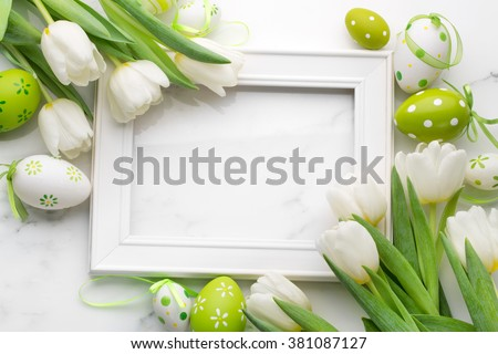 Tulip,easter eggs and blank picture frame on white marble background - stock photo