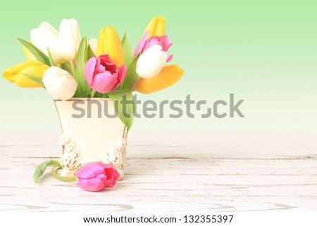 Tulip flowers in a vintage little vase. - stock photo