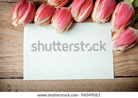 Tulips and blank card on old wooden boards - stock photo