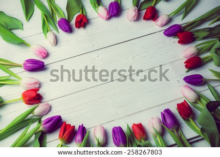 Tulips forming frame on wooden table - stock photo