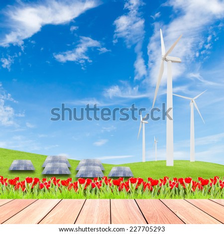 tulips with wind turbine and solar panels on green grass field against blue sky background and wood plank foreground,used for green earth concept - stock photo