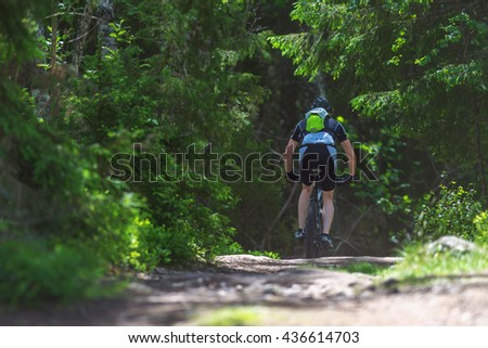 TULLINGE, SWEDEN - JUNE 12, 2016: Back of a MTB cyclist competing in the forests at Lida loop during summer. One of swedens biggest mountainbike races. - stock photo