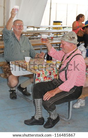 TULSA, OK - OCT 20: Party goers drink beer and sing songs at Oktoberfest in TULSA, OK, on October 20, 2012 in TULSA, OK.  Tulsa is the origin of the Chicken Dance now so popular at the Oktoberfest. - stock photo