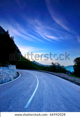 Tumbling of the road on background dawning sky - stock photo