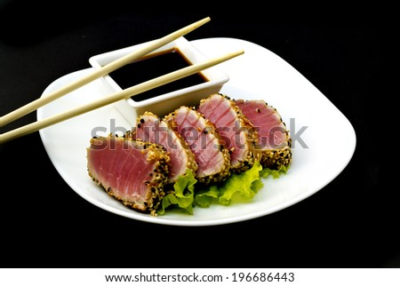 Tuna fillet with sesame soy sauce and chopsticks on a big white plate over black background - stock photo
