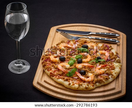 Tuna pizza with shrimp and water, cutlery, top view - stock photo