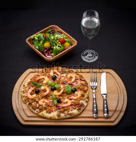 Tuna pizza with shrimp, salad and water, cutlery, top view - stock photo
