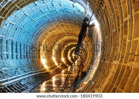 Tuneller welder working with electrode at arc welding in underground subway metro construction site - stock photo