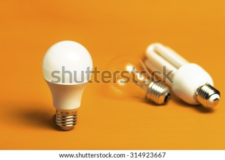 Tungsten,fluorescent and LED bulbs isolated on a orange background - stock photo