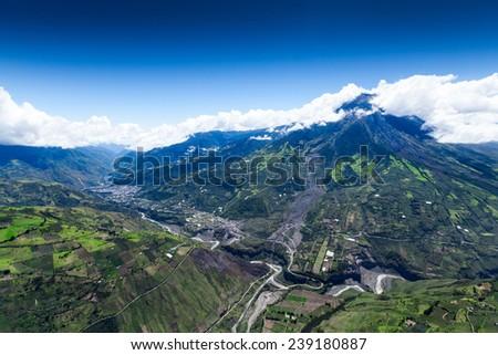 Tungurahua volcano high altitude aerial wide shot, city of Banos de Agua Santa on the far left, visible crater - stock photo
