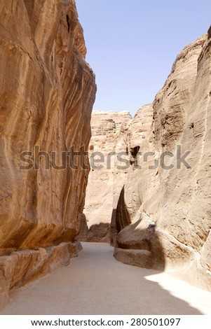 Tunnel between the rocky mountains to the ancient city of Petra, Jordan. - stock photo