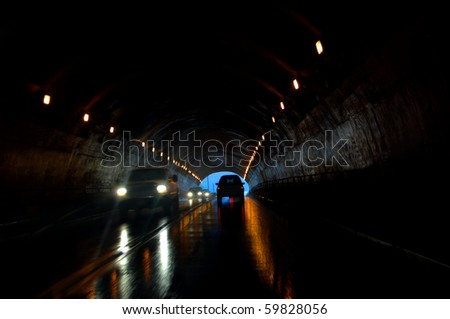 Tunnel traffic has added danger of wet roads.  Headlights throw rays of light in front of truck. - stock photo