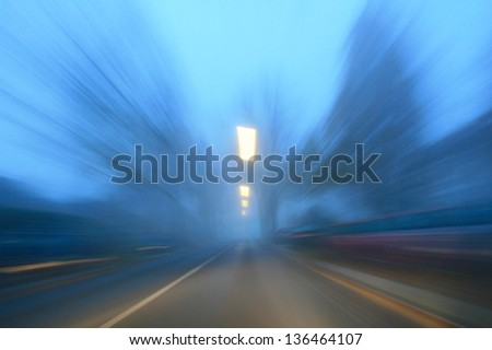 Tunnel vision of a road with motion blur during fall - stock photo