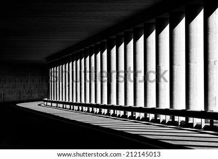 Tunnel with columns in black and white photo, abstract tunnel photo, black and white photo, architecture details close up in black and white, way, road, columns, diagonal, street photography - stock photo