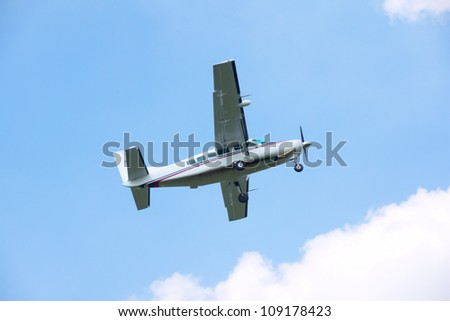 Turboprop airplane taking off in blue sky - stock photo