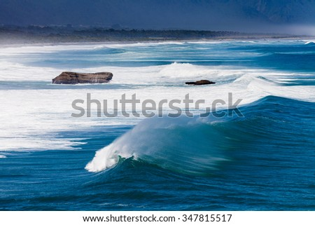 Turbulent water of breaking ocean waves and spray on incoming ocean surf on West Coast of New Zealand South Island - stock photo