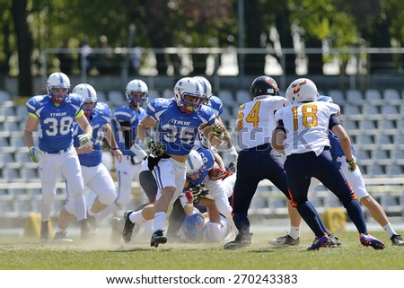 TURIN, ITALY - APRIL 12, 2015: CUOMO Valerio (center) runs during Italy vs Spain U19 american football match, in the Nebiolo Stadium in Turin. - stock photo