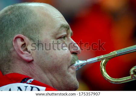 TURIN, ITALY FEBRUARY 20, 2006: Dutch fan blowing the trumpet to support his national team during the Speed ice Skating competition at the Winter Olympic Games of Turin 2006. - stock photo
