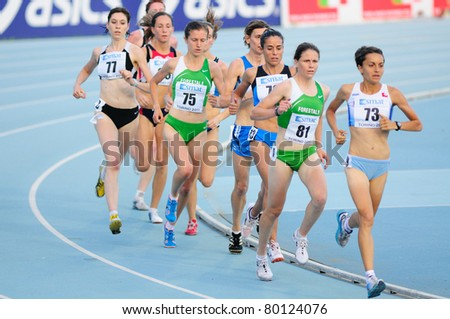 TURIN, ITALY - JUNE 26: Agne Tschurtschenthaler (No. 81) and Martina Facciani (No. 73) lead the pack during 5,000m women's race at 2011 Track and Field Italian Championship on June 26, 2011 in Turin, Italy. - stock photo