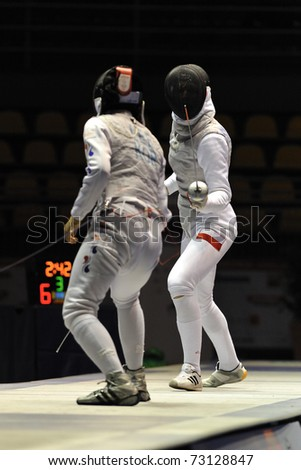 TURIN, ITALY - MARCH 13: LEE (KOR) fight against GRUCHALA Sylwia (POL) during team tournament semifinal match of the 2011 Women world fencing cup on March 13, 2011 in Turin, Italy - stock photo