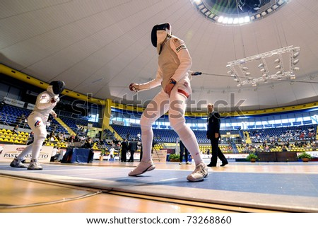 TURIN, ITALY - MARCH 13: Unknown Poland and Russia athlete fight during team tournament final match of the 2011 Women world fencing cup on March 13, 2011 in Turin, Italy - stock photo