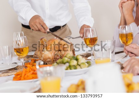 Turkey being carved at celebratory holiday dinner - stock photo