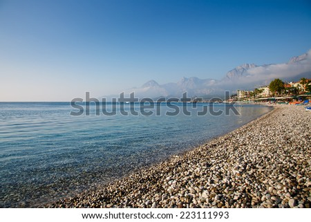 Turkey, Kemer, beach- sea- sun beds - mountains - clouds - stock photo