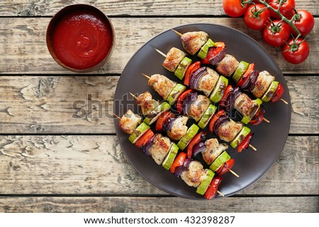 Turkey or chicken meat skewers shish kebab with onion tomatoes and ketchup on vintage wooden table background. Traditional barbecue grill food - stock photo