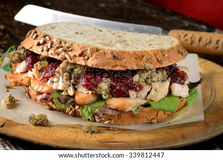 Turkey sandwich with stuffing and cranberry sauce. Freshly made from Christmas turkey leftovers on crusty wholemeal bread. - stock photo