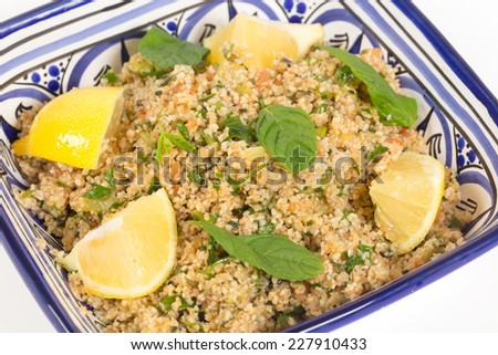 Turkish bulgur wheat salad, known as kisr, made with mint, cucumber,  lemon, romato and parsley, seen from a high angle - stock photo