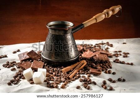 Turkish coffee among coffee beans, cinnamon and chocolate. - stock photo