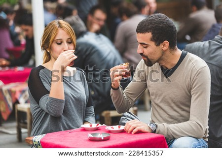 Turkish Couple Drinking Cay, Traditional Tea, in Istanbul. Cay is served in small glasses and People drink it everytime during the day.  - stock photo