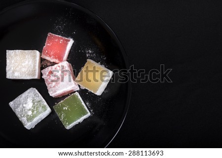 Turkish delight pieces on dark plate over black background - stock photo