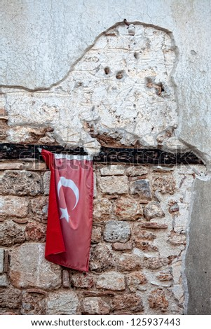 Turkish flag hanging on ancient stone wall - stock photo