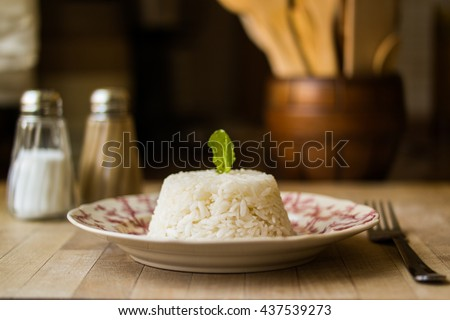Turkish pilaf-rice with salt and black pepper on a wooden surface in the kitchen front view - stock photo