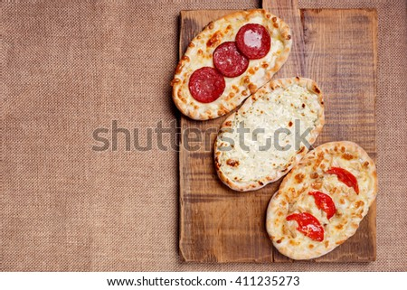 Turkish pita bread with cottage cheese, chicken, salami and tomatoes on a wooden cutting board. Mini pizzas - stock photo