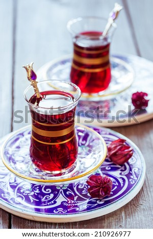 Turkish pomegranate tea in a traditional glasses. Toning in vintage style. Closeup with shallow DOF  - stock photo