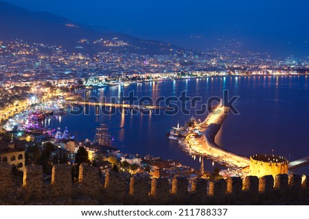 Turkish riviera - Alanya city center, Kizil Kule (Red Tower) and harbor. Night view from Alanya Castle  - stock photo
