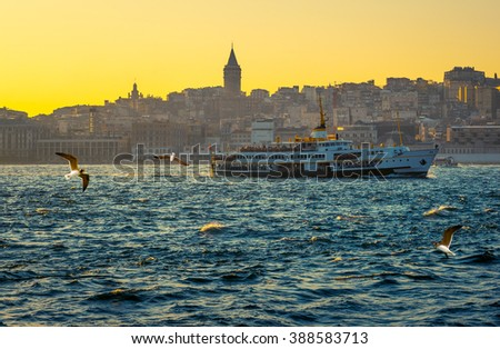 Turkish steamboat and Istanbul cityscape at golden sunset. Passenger ship and seaside view on Galata Tower, travel to Istanbul. Sea voyage on the old ferryboat, Istanbul's water transport. - stock photo