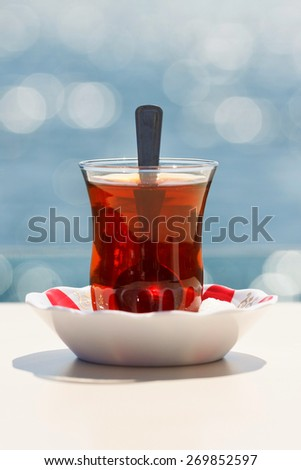 Turkish tea against the sea - stock photo