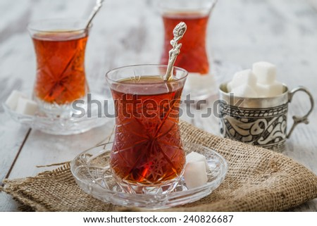 Turkish tea served in traditional glasses on white wooden background - stock photo