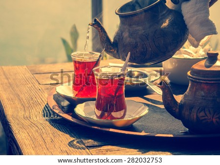 Turkish tea with authentic glass cup and copper tea kettle. Two cups of turkish tea,  toned with vintage instagram filter effect. Istanbul cafe with oriental culture of the street food. - stock photo