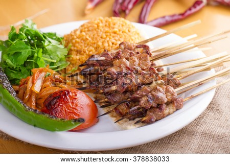 Turkish Traditional Sis Kebab in a plate on wooden table with garnish - stock photo