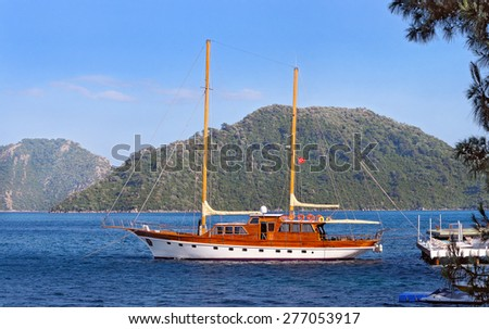Turkish wooden yacht near a pier against the hills covered with the trees and the blue sky - stock photo