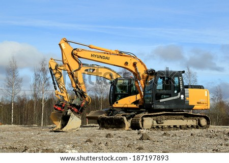 TURKU, FINLAND - APRIL 12, 2014: Cat and Hyundai Robex excavators at construction site. The market share for Hyundai Heavy Industries Europe increased with more than 30% in 2013. - stock photo
