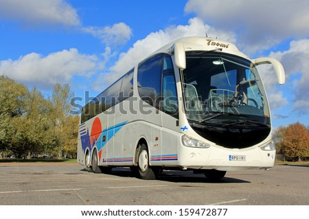 TURKU, FINLAND - OCTOBER 19: Scania coach bus on a parking lot on October 19, 2013 in Turku, Finland. Scania currently conducts field tests with 4 hybrid buses in Sweden and in southern Europe.   - stock photo