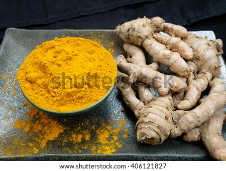 Turmeric powder and fresh turmeric roots on wooden. - stock photo