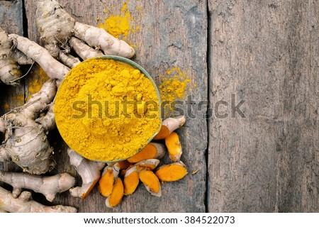Turmeric powder and turmeric on wooden background .- Vintage Filter Processing. - stock photo