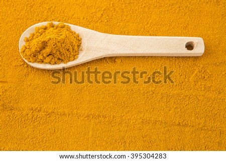 Turmeric powder and wooden spoon - stock photo