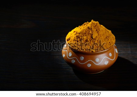 Turmeric powder in clay pot on black background - stock photo